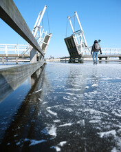 People Skate Through Drawbridge In Kinderdijk On Frozen Water Of Canal On Sunny Winter Day In Holland