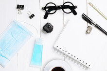 Flat Lay, Top View Office White Table Wooden Desk. Workspace With Blank Eyeglasses, Diary, Mask, Alcohol Gel And Smartphone On Background. Work From Home.
