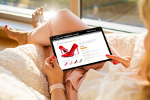 Woman Shopping For New High Heel Shoes Online On Tablet At Home