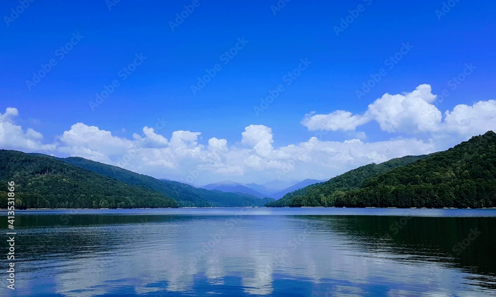 Fototapeta Scenic View Of Lake And Mountains Against Blue Sky