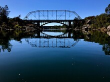 Arch Bridge Over Lake Against Blue Sky