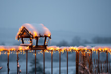 Wooden Birdhouse Covered By Snow, With Glowing Christmas Lights Placed In Small Roof Garden.