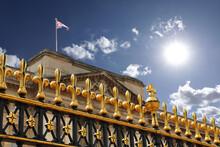 Primo Piano Della Cancellata Di Buckingam Palace A Londra, Sul Tetto Sventola La Union Jack, La Bandiera Inglese E Sullo Sfondo Il Sole E Il Cielo Azzurro