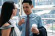 canvas print picture - Businessman explaining something to a businesswoman and holding cup of coffee. Close up photo of handsome business man talking with female coworker in office with big windows