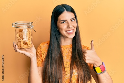 Canvas Print Young hispanic woman holding jar with uncooked pasta smiling happy and positive,