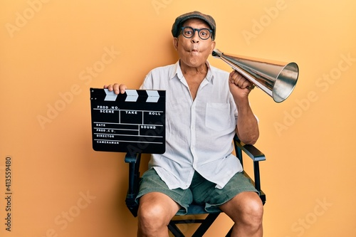 Photo Handsome mature director man holding video film clapboard and louder making fish face with mouth and squinting eyes, crazy and comical