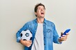 Handsome caucasian man holding football ball looking at smartphone angry and mad screaming frustrated and furious, shouting with anger looking up.