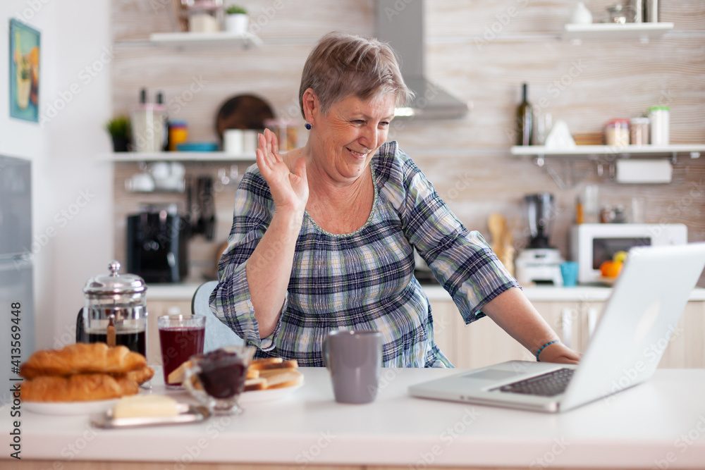 Fototapeta Retired woman waving during online meeting with family on video call using laptop in kitchen having breakfast. Elderly person using internet online chat tech, pc webcam for virtual conference call