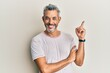 canvas print picture - Middle age grey-haired man wearing casual clothes with a big smile on face, pointing with hand and finger to the side looking at the camera.