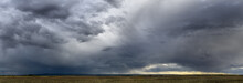 Dramatic Blue-gray Storm Clouds Over A Very Wide Panoramic Prairie Landscape With A Gravel Road Extending Off Into The Distance.