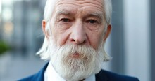 Portrait Of Caucasian Old Gray-haired Man Standing Outside And Looking At Camera With Sad Eyes. Sadness Concept. Close Up Of Retired Male Pensioner Businessman With Upset Face.
