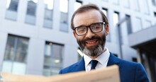 Caucasian Middle-aged Man In Glasses And Tie Standing Outside And Reading Newspaper With Smile. Business Media Concept. Rich Elegant Male Businessman Read News In Paper At Street In City.