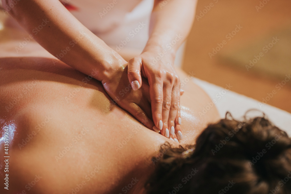Fototapeta Woman getting massage treatment against back pain in the spa salon