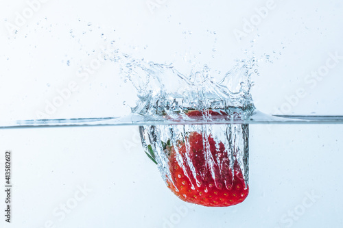 Fotografering Closeup of a ripe strawberry falling into the water against a gray background
