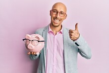 Bald Man With Beard Holding Piggy Bank With Glasses Smiling Happy And Positive, Thumb Up Doing Excellent And Approval Sign