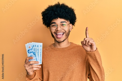 Fototapeta Young african american man with afro hair holding 50 thai baht banknotes smiling