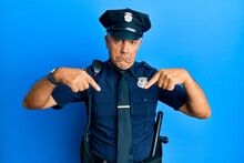 Handsome Middle Age Mature Man Wearing Police Uniform Pointing Down Looking Sad And Upset, Indicating Direction With Fingers, Unhappy And Depressed.