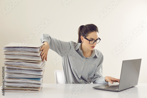 Fototapeta Young accountant working on laptop computer sitting at desk with pile of papers. Paperwork vs electronic documents. Storing files in digital database. Having quick convenient access to storage system obraz