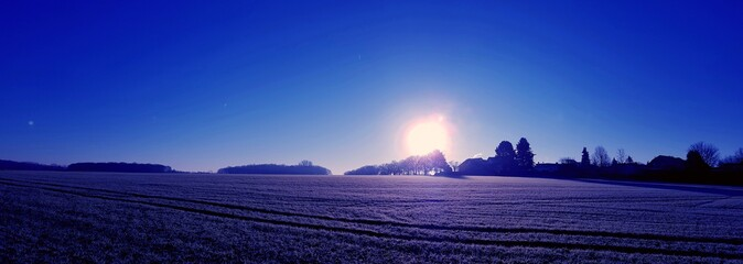 Scenic View Of Field Against Clear Blue Sky During Sunset