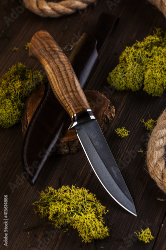 Fotografia Hunting knife made of damascus steel on wooden background