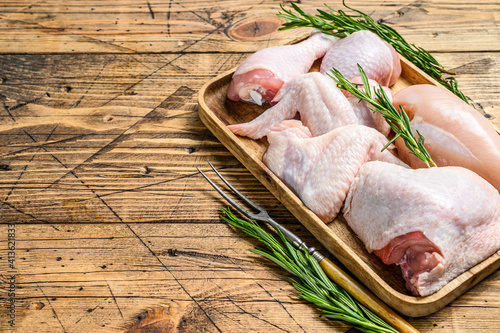 Obraz Fresh raw chicken meat, wings, breast, thigh and drumsticks on a wooden tray. Wooden background. Top view. Copy space - fototapety do salonu