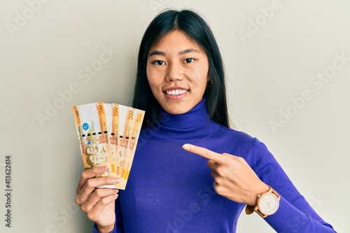 Obraz na plátne Young chinese woman holding 500 philippine peso banknotes smiling happy pointing