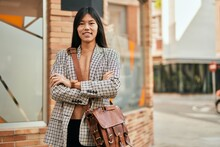 Young Asian Businesswoman With Arms Crossed Smiling Happy At The City.