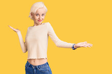 Young Blonde Woman Wearing Casual Clothes Clueless And Confused Expression With Arms And Hands Raised. Doubt Concept.