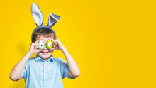 Happy Child Is Wearing Bunny Ears And Holding Colorful Easter Eggs With Painted Eyes On Them In Front Of His Eyes On A Yellow Background