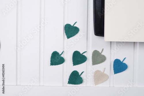 Fototapeta Biały drewniany blat listki zielone talerz czarny obraz
