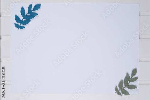 Obraz Kartka papieru biała na białym blacie drewnianym z listkami zielonymi - fototapety do salonu