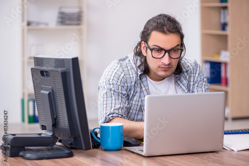 Fototapeta Young male it specialist working in the office obraz
