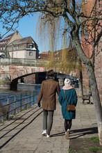 Couple Walking In Border Il River At Little France Quarter In Strasbourg