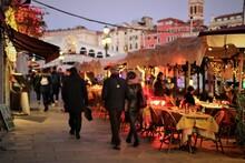 People Walking On Street In City At Dusk
