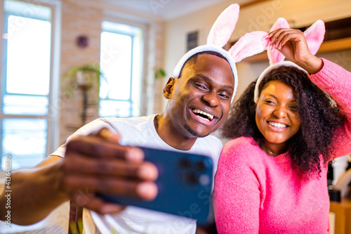 Fototapeta Young african american man and woman wearing cute easter bunny ears in the house taking selfie on smartphone obraz