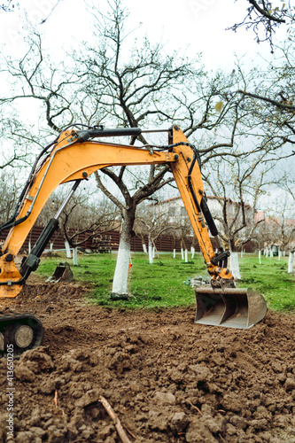 Fototapeta Landscaping works at home construction site using excavator and mini bulldozer obraz