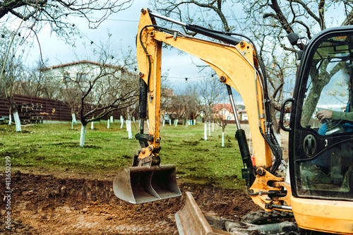 Fototapeta Landscaping works in the garden at construction site with mini yellow excavator obraz