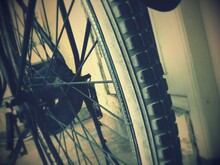 Cropped Tire Of Bicycle Parked By Wall