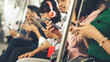 Leinwandbild Motiv Young people using mobile phone in public underground train . Urban city lifestyle and commuting in Asia concept .