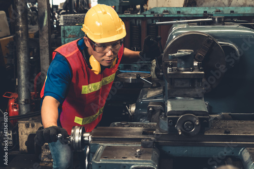 Fototapeta Skillful factory worker or engineer do machine job in manufacturing workshop . Industrial people and manufacturing labor concept . obraz