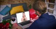 Caucasian couple on a valentines date video call smiling woman on laptop screen holding flowers