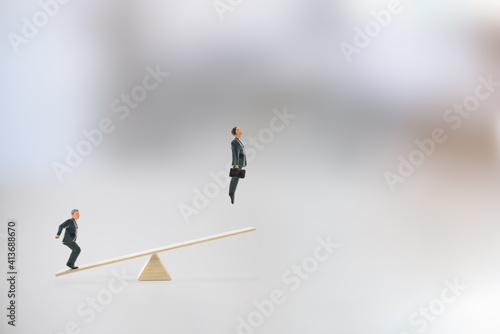 Business partnership and cooperation for ultimate success, motivation concept : Colleague steps on a seesaw sending a friend flying high above into the air, depicts team spirit for getting a job done