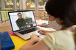 Caucasian schoolgirl wearing face mask using laptop on video call with male teacher