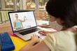 Caucasian schoolgirl wearing face mask using laptop on video call with female teacher