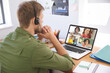 Caucasian male teacher using laptop and phone headset on video call with school children learning fr