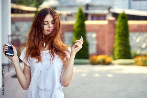 Fototapeta cheerful woman in a white t-shirt walks down the street with headphones rest obraz