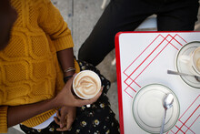 Overhead View Of Woman Holding Cappuccino While Sitting In Sidewalk Cafe