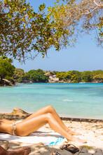 Low Section Of Woman Sunbathing On Beach