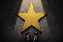 Success In Business Or Personal Talent Concept. Top View Of Business Person In Working Shoes Standing In Front Of A Golden Star. Light Shining On The Dark Cement Floor