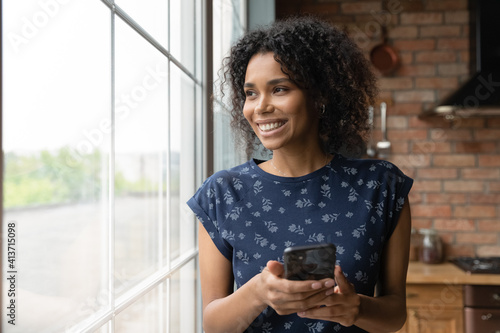 Fototapeta Close up dreamy smiling African American woman holding smartphone, looking out window, visualizing, distracted from phone, chatting online with boyfriend or waiting for call, enjoying leisure time obraz